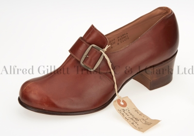 Cover shot showing a single women's brown leather monk shoe with original label attached; Clarks 'Canford Side Buckle', 1946-1947 ©Alfred Gillett Trust / C & J Clark Ltd